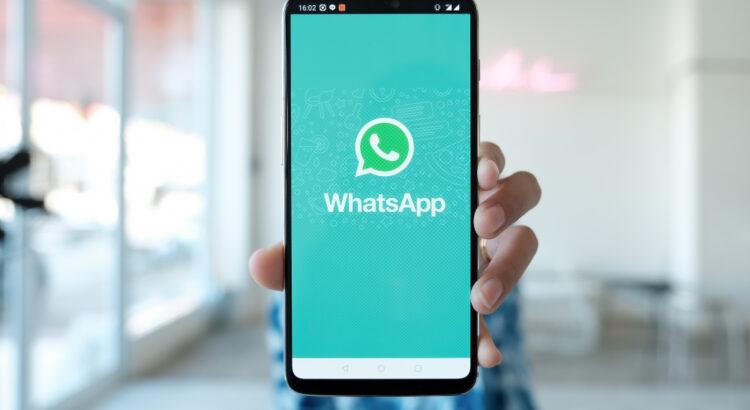 Homem mostrando smartphone com logotipo do WhatsApp