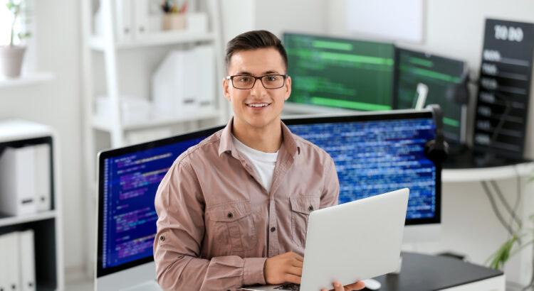 Programador em frente a computadores mostrando o trabalho de outsourcing de TI