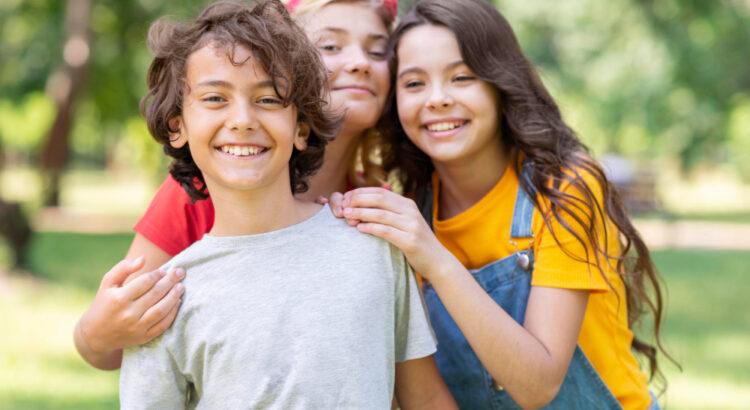 Três crianças olhando para a foto e sorrindo